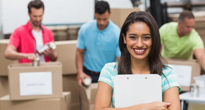 smiling woman holding a clipboard and behind her men are packing boxes