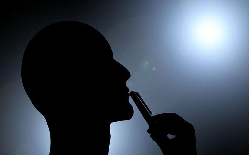 silhouette of man's head with pen touching his lips