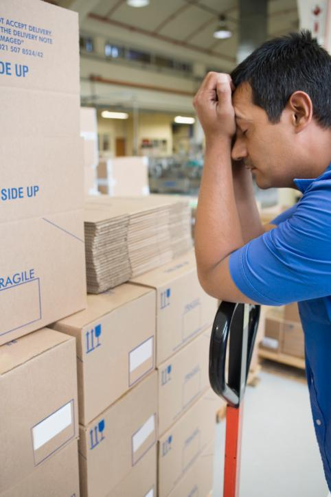 sleepy man resting his head in his hands as he stands beside a stack of boxes in a warehouse