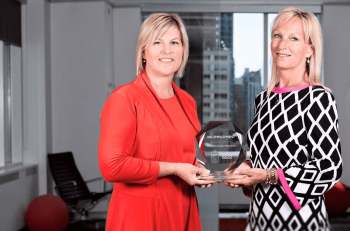 ABL's 2 founders holding a glass award trophy