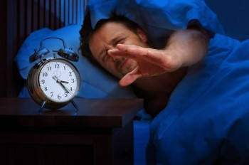 sleepy man in bed reaches for his alarm clock