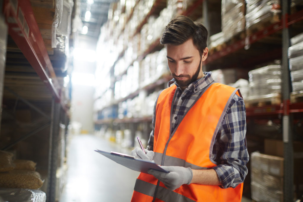 man in reflective vest writing on a clipboard in a warehouse