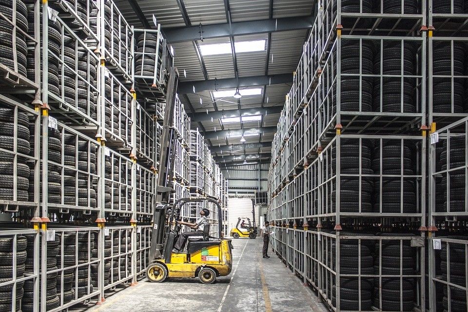 internal view of a tire warehouse and forklift removing a pallet of tires