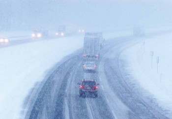 cars on a very snowy highway