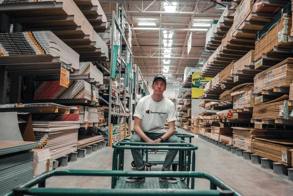 young man sitting on a cart in a lumber warehouse