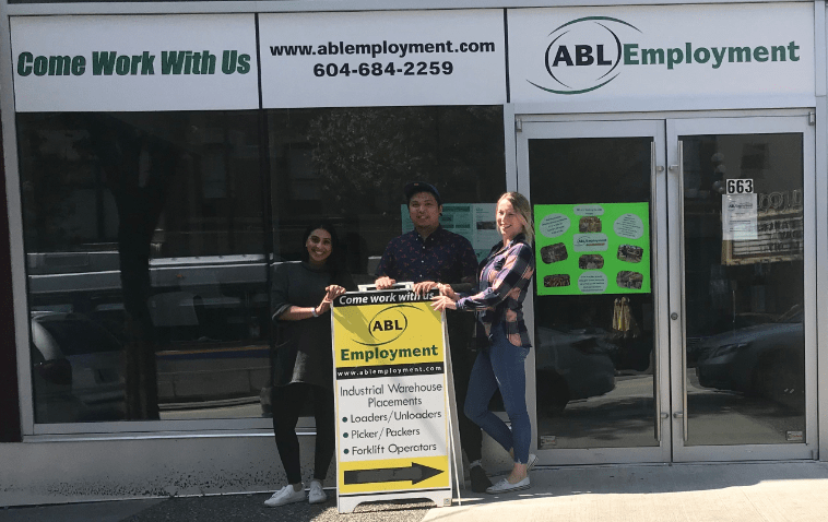 Staff members posing outside exterior of office space with sandwich board sign