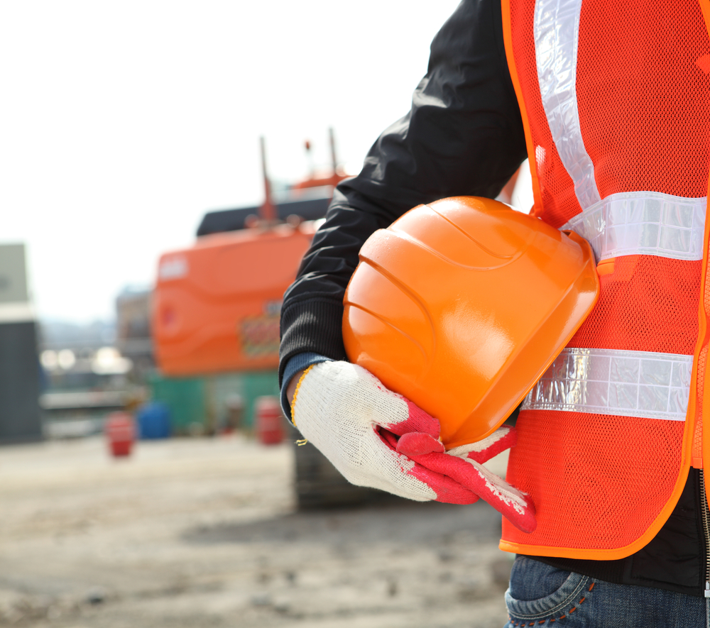 person in reflective PPE holding a hard hat outside