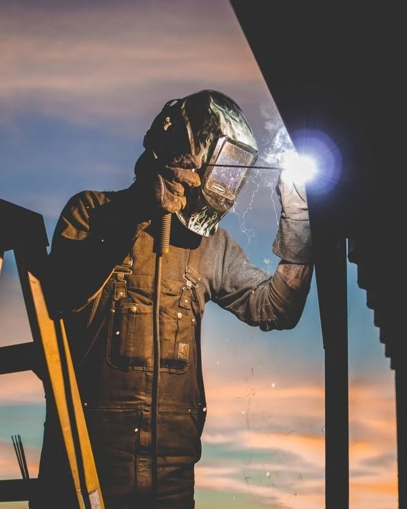 Worker welding wearing Welding helmet and overalls
