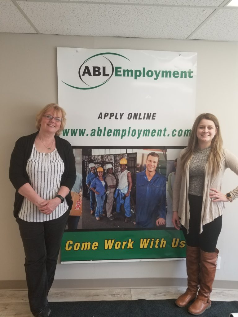 2 Stratford staff members standing beside an ABL roll-up sign