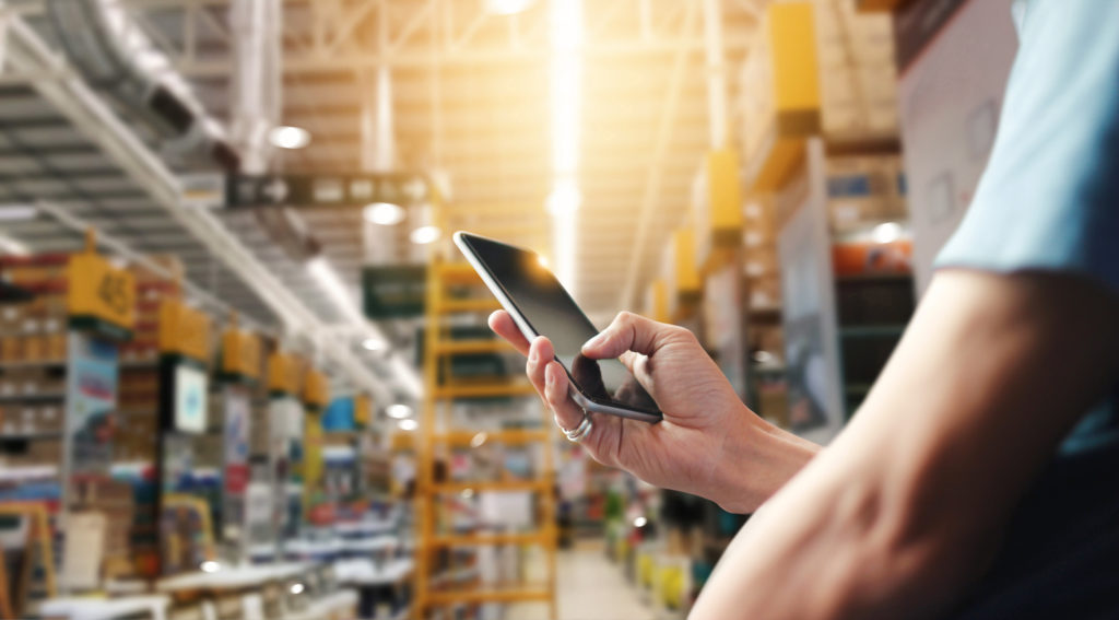 Factory worker using application on mobile smartphone to operate automation for modern trade. Checking order in large warehouse. Import and export the shipping cargo.
