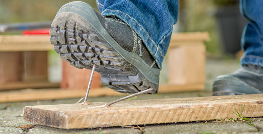 Worker with safety boots steps on a nail