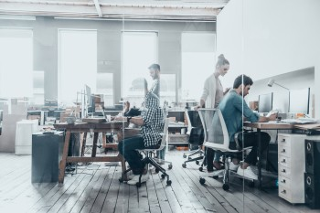 people working in a brightly lit open concept workspace