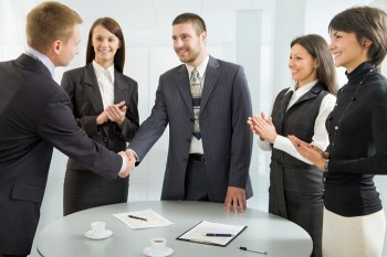 5 people gathered around a round table, some clapping, some shaking hands.