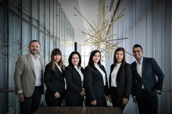 4 women and 2 men standing beside one another in a corporate team photo shot