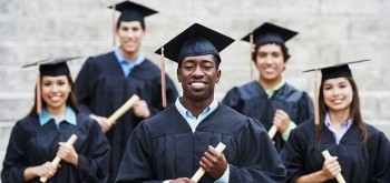 graduating students outside in caps and gowns with diplomas