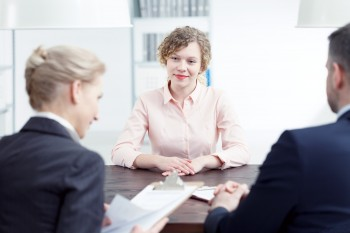 woman being interviewed by two people in suits
