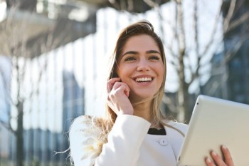 woman smiling while talking on a cellphone outside