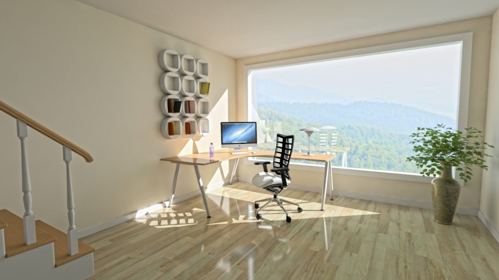 a bright, sunny home office space with a window overlooking forested mountains