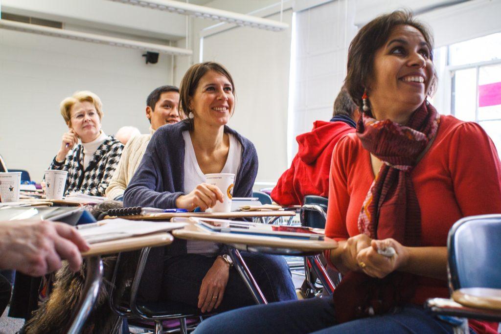 adult students smiling while huddled grouped together at desks