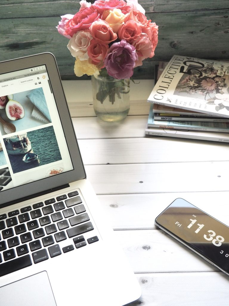 a casual home office desk with roses in a vase, magazines, laptop, and cell phone.