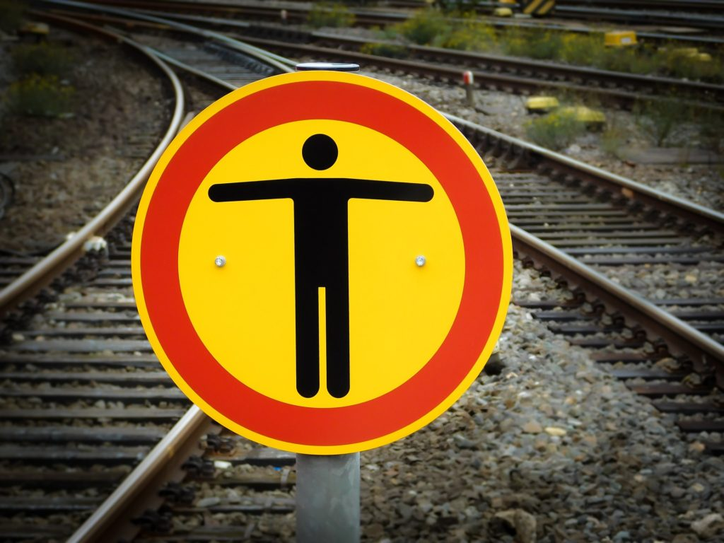 railway tracks converging and a yellow and red warning sign