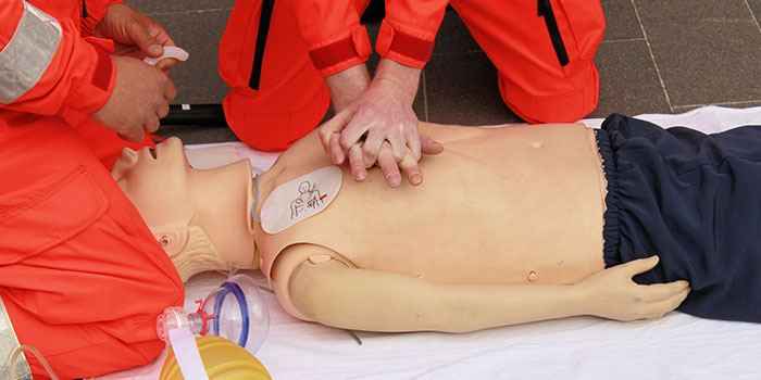 CPR training manquin being worked on by trainees learning to do chest compressions
