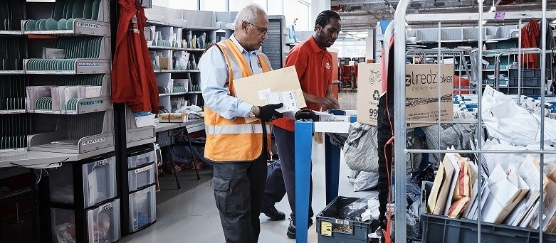 two men in warehouse sorting mail packages