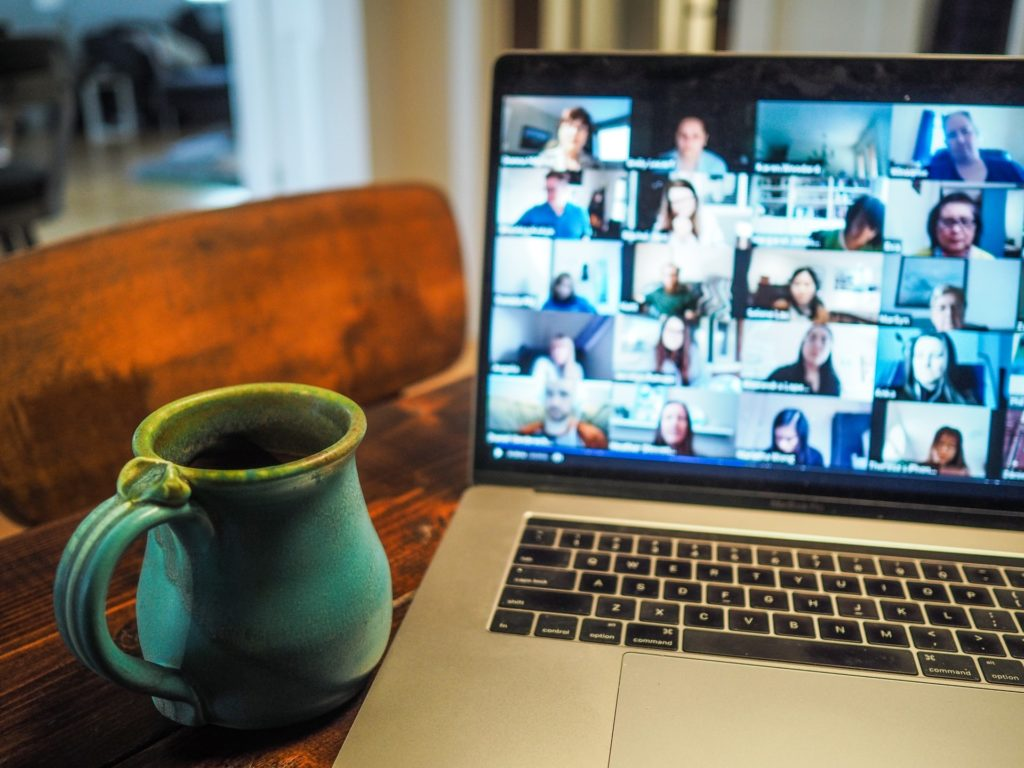 laptop displaying virtual meeting participants with coffee mug beside it