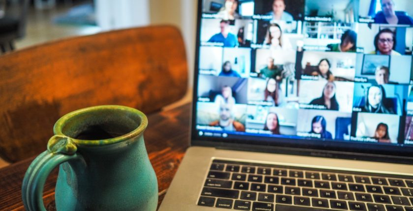 laptop displaying virtual meeting participants with coffee mug beside it