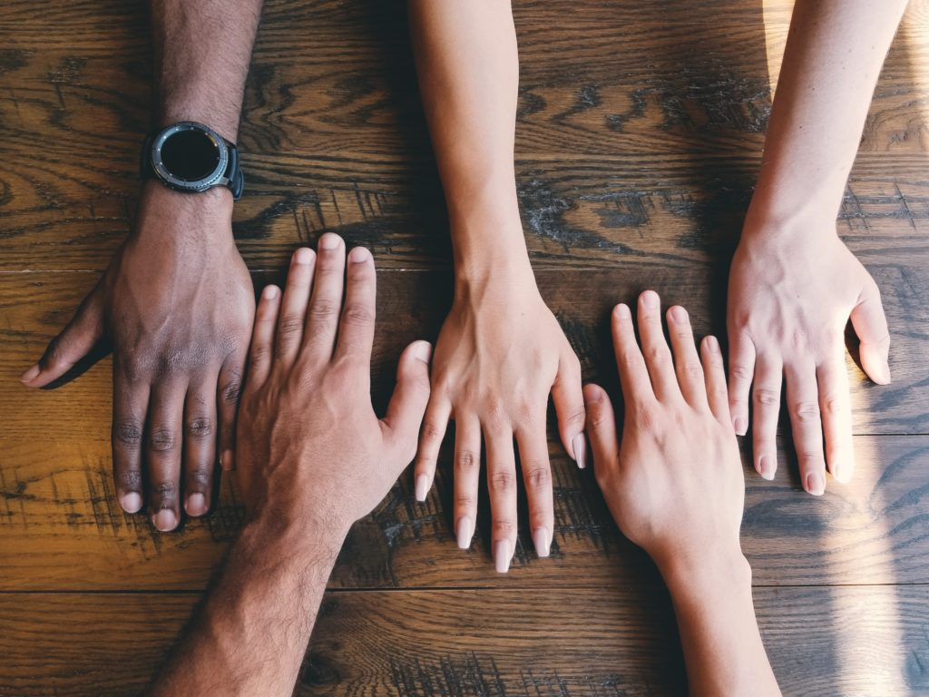 multiple hands of people with different skin tones resting on a tabletop