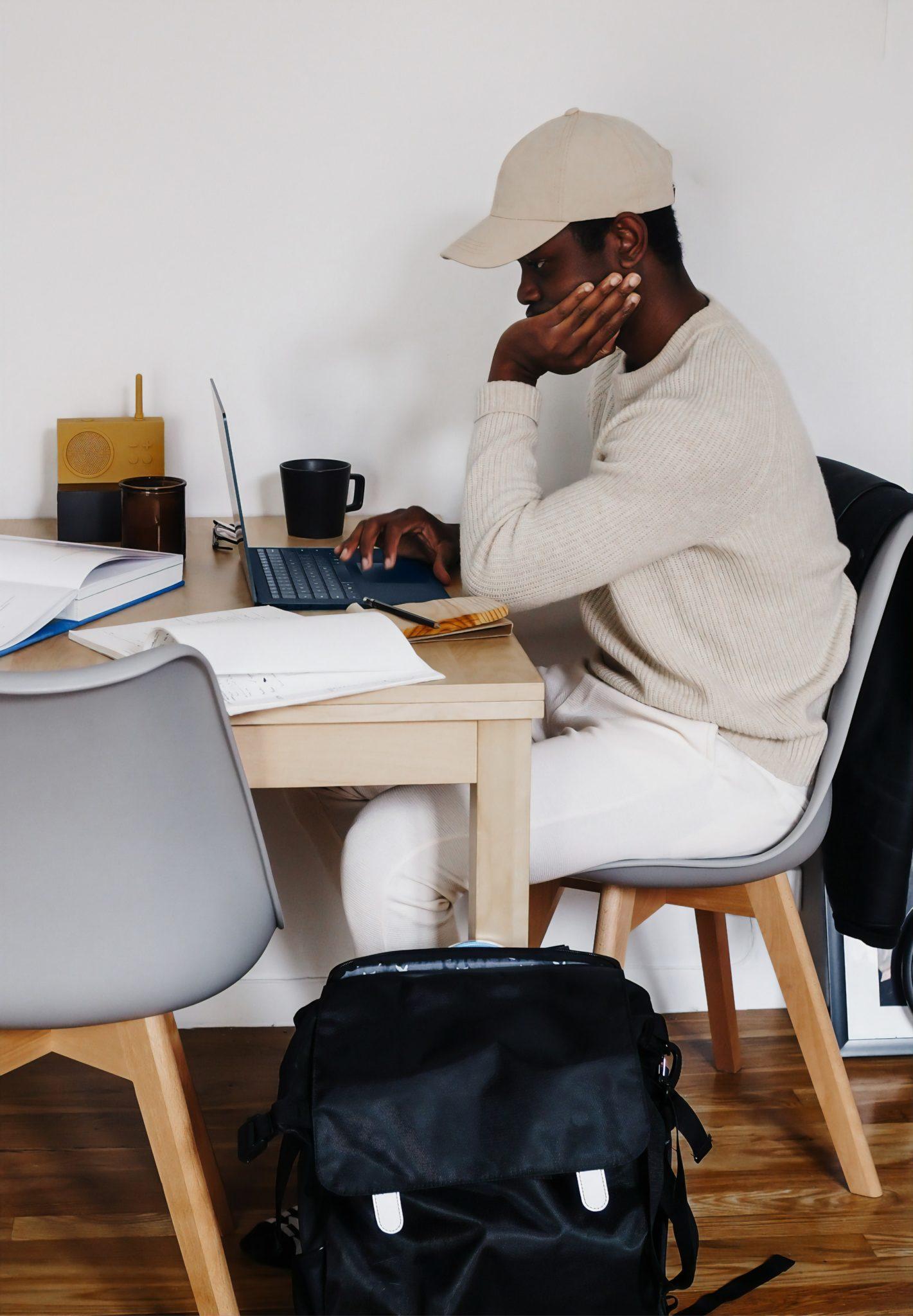 man wearing baseball cap sitting at desk with laptop