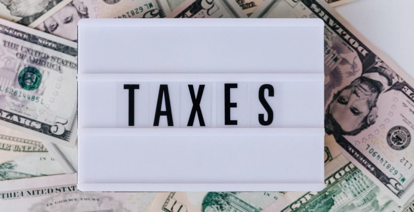 "word ""taxes"" on a white sign, resting on a bed of banknotes"