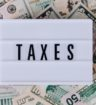 """word """"taxes"""" on a white sign, resting on a bed of banknotes"""