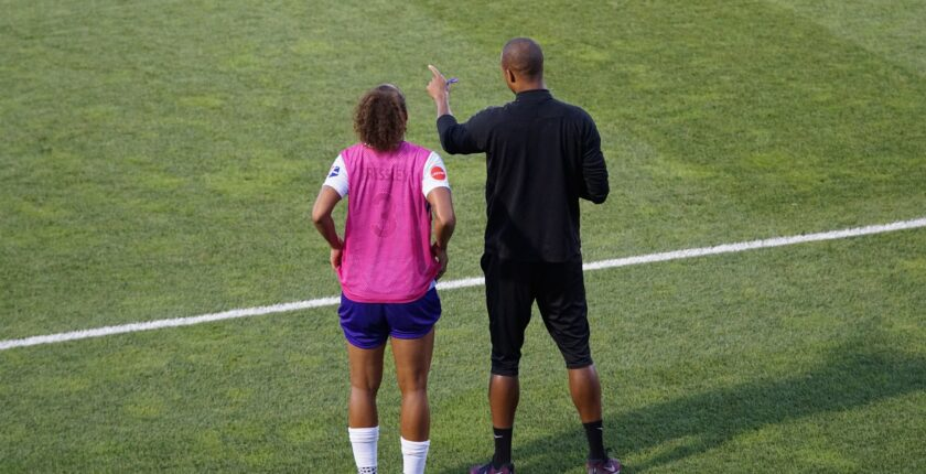 Soccer player being instructed by coach