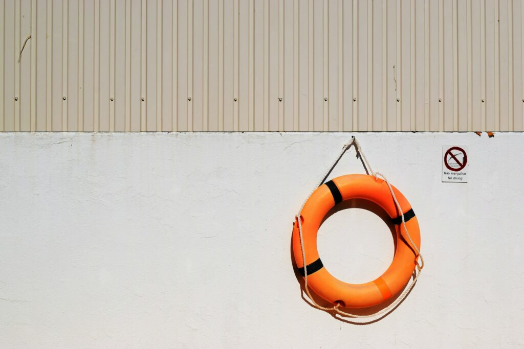 Orange life saver bouy hanging on a wall.