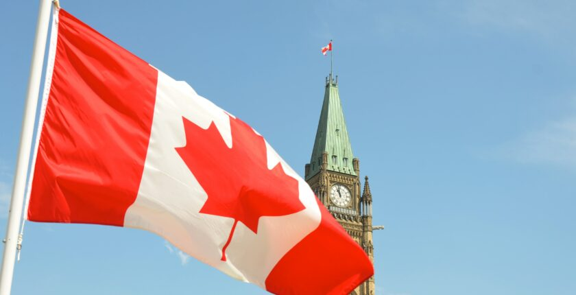 Canadian flag, parliament building in background