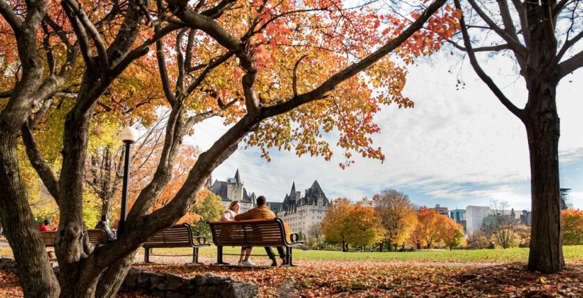 2 people sit on a park bench with Canadian parliament building in background