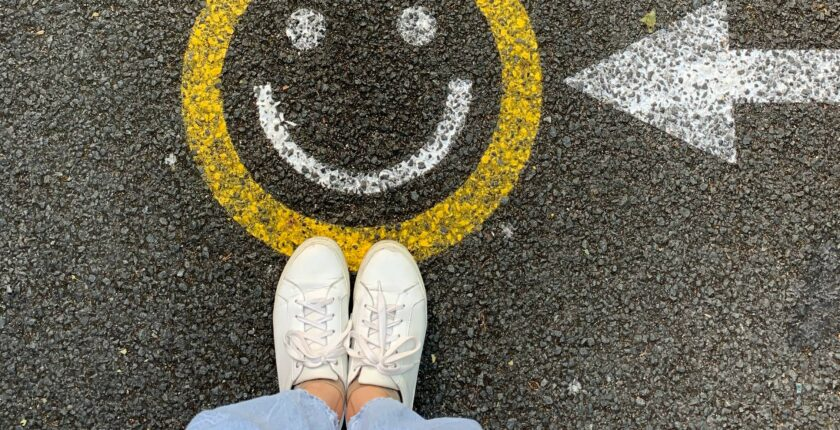 smiley face painted on the road with person standing next to it.